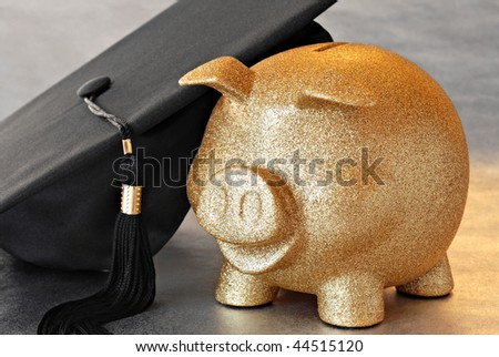 Higher education conceptual image of gold piggy bank with graduation cap on reflective surface.  Macro with shallow dof.  Focus on the bank. - stock photo