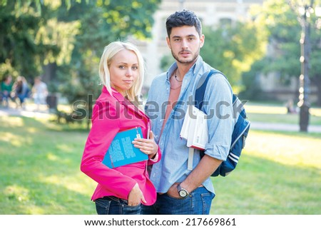 Higher education. Couple of students standing together holding books looking at the camera while standing on the grass against the building of the university - stock photo