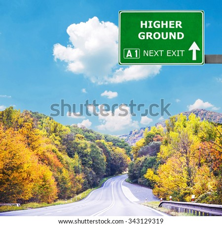 HIGHER GROUND road sign against clear blue sky - stock photo