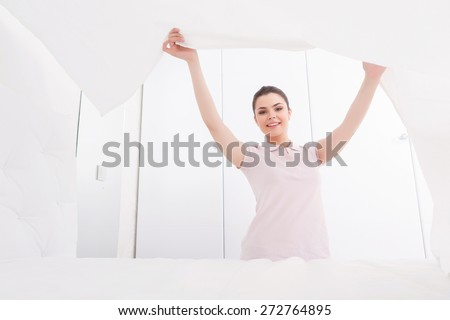 Higher means better. Young female is elegantly making bed in totally white bedroom by lifting blanket - stock photo