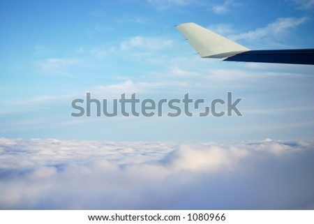Higher than the sky - soft clouds with the tip of an airplane wing visible