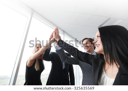highfive in a business meeting - stock photo