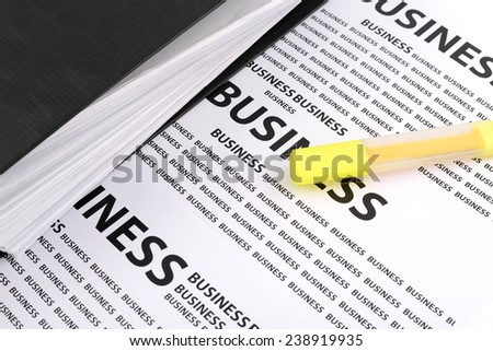 Highlighter and a file folder with documents on documents business