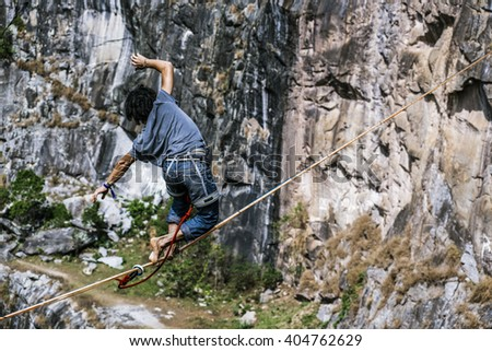 Highliner athlete walking over a rock mountain in a tight rope
