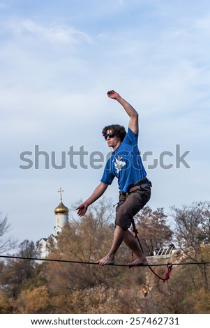 Highliner balancing on tightrope, nearly falling - stock photo