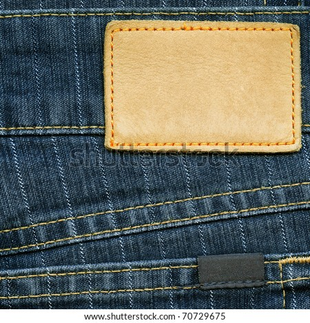 Highly detailed closeup of blank grungy leather label and small dark cotton label on striped blue denim, good for background - stock photo