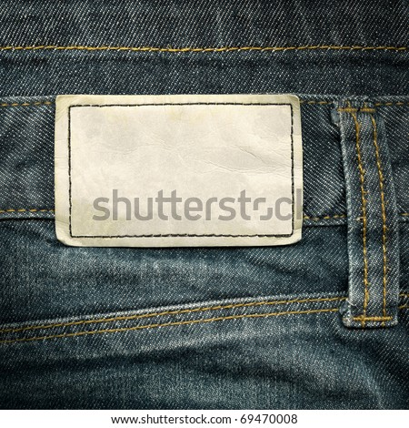 Highly detailed closeup of blank grungy leather label on vintage gray denim with yellow seams, good for background - stock photo