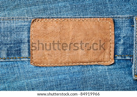 Highly detailed closeup of blank grungy leather label on worn blue denim with orange seams, good for background