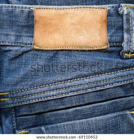 Highly detailed closeup of blank grungy stained leather label on old blue jeans with lot of seams, some kind of background - stock photo