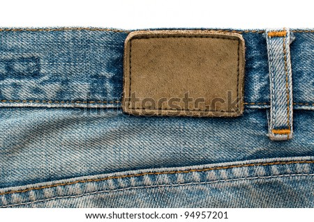 Highly detailed closeup of blank grungy stained leather label on old blue jeans with lot of seams, some kind of background