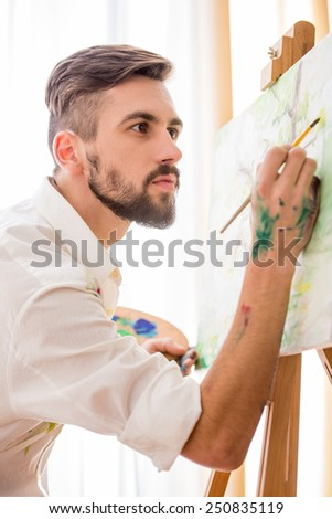 Highly gifted painter is painting his picture with brush and palette. Close-up. - stock photo