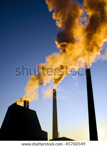 Highly polluted smoke escaping from industrial chimneys - stock photo