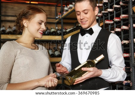 Highly recommend. Professional sommelier showing his female client a bottle of white wine