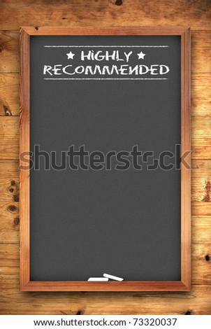 highly recommended chalkboard on wooden background - stock photo