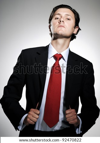 Highly successful business man in suit poses pulling his suit lapels with an arrogant tilt to the chin - stock photo