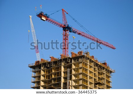 Highrise building construction site with tower cranes above it. - stock photo