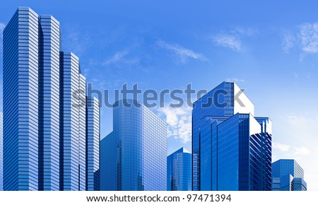 highrise glass skyscraper buildings skyline in blue dominant against a partially clouded sky - stock photo