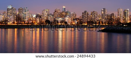 Highrises glow in gathering dusk on a winter Vancouver evening by the English Bay