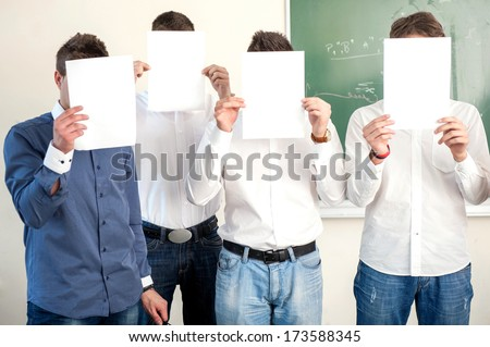 Highschool boys holding white papers in front of their heads - stock photo