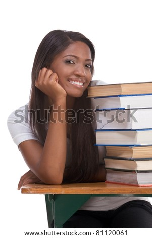 Highschool or college ethnic African-American student sitting by the desk with lot of books in class or library - stock photo