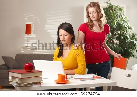 Highschool students learning at home looking at laptop computer at table. - stock photo