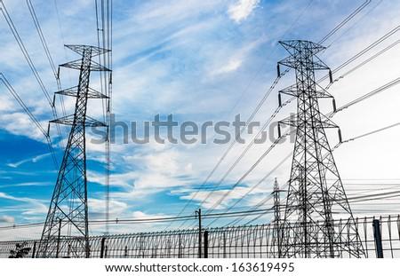 Hight Voltage Electricity Pylon on Blue Sky Background - stock photo