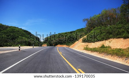 Highway along mountain and blue sky - stock photo