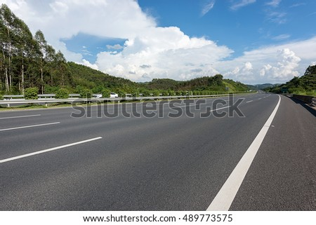 Highway asphalt pavement in the blue sky white cloud background