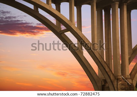 Highway Bridge Arch And Structural Supports Against A Red Evening Sky, The Little Miami River, Ohio, USA - stock photo