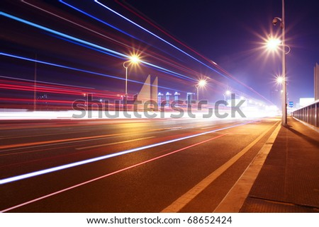 highway bridge at night with traces of light traffic - stock photo