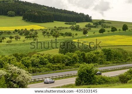 highway in hilly green countryside of Baden Wuttenberg with woods, meadows and rapeseed fields, shot under cloudy yet bright sky near Geisingen, Germany