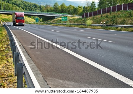 Highway in landscape, red truck arrives on the highway, in the background the bridge and forest, on the slope of the against the sound barrier - stock photo