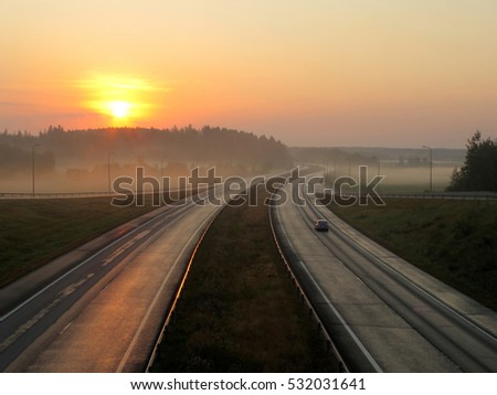 Highway in the early morning at sunrise in the mist