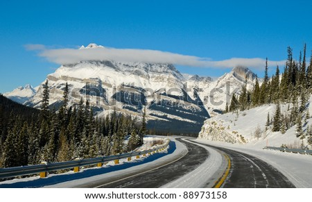 Highway in Winter through mountains little traffic - stock photo
