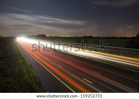 highway / motorway car light trails - stock photo