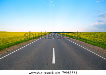 Highway of flowering fields and blue sky - stock photo