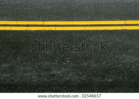 Highway pavement with painted yellow lines.