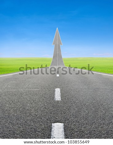 highway road going up as an arrow over green field and blue sky - stock photo
