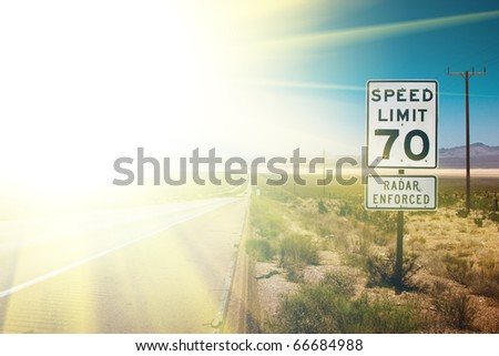 Highway road to sunrise. 70 MPH speed limit sign. - stock photo