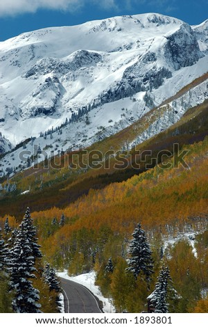highway route through autumn colors and snow covered mountain - stock photo