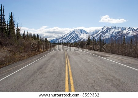 Highway running by the Alaska Range - stock photo