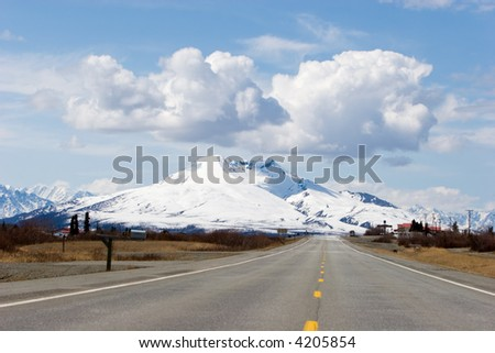 Highway running by the snowy Alaska mountains - stock photo