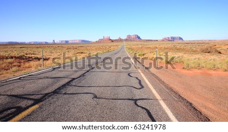 Highway stretches out in desert with rock formations of Monument Valley visible on the distant horizon - stock photo