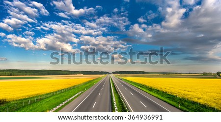 highway through fields of rapeseed - stock photo