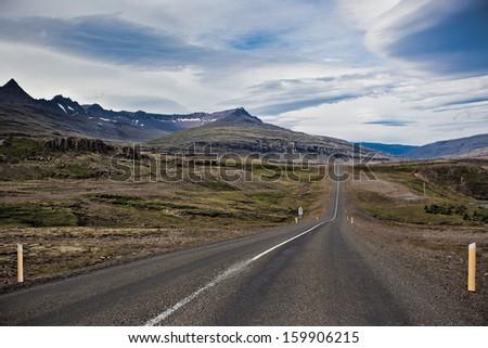 Highway through Iceland landscape at overcast day. Horizontal shot - stock photo