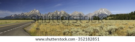 Highway to Grand Tetons. Blue sky golden field majestic view of mountains and green forest in background. Panoramic.   - stock photo