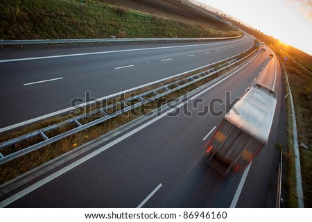 highway traffic - motion blurred truck on a highway/motorway/speedway at dusk (color toned image) - stock photo