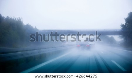 Highway traffic on a rainy day on German European autobahn with cars driving over 200 kmh - stock photo