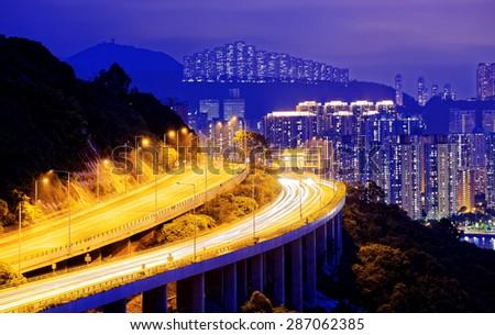 highway traffic road to city downtown at night, hong kong city - stock photo