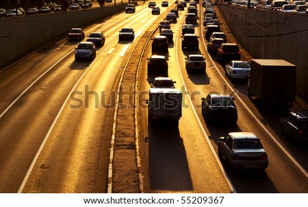Highway with lots of cars. Red sunset light and high contrast colors. - stock photo